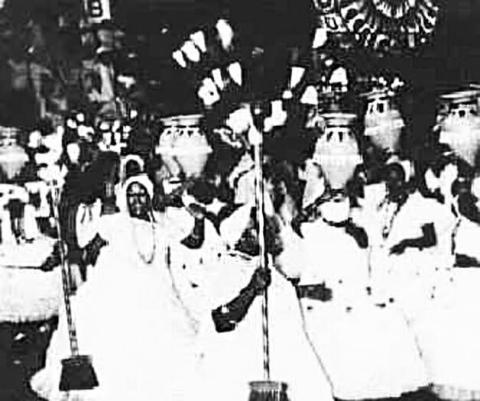 Imagem em preto e branco, onde mostra mulheres negras caracterizadas como baianas com vassouras nas mãos
