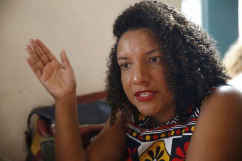 Deputada Renata Souza, mulher negra de cabelo cacheado, sentada gesticulando.