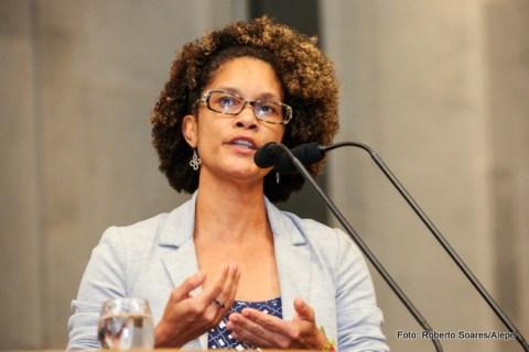 Deputada Jô Cavalcanti, mulher negra de cabelo cacheado e usando óculos, em pé discursando.