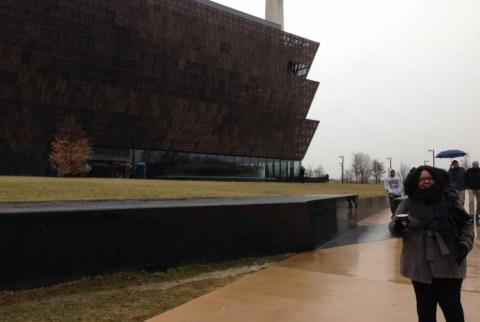 Carolyne Oliveira - mulher negra, de cabelo crespo, vestindo casaco marrom - pousando ao lado de um prédio