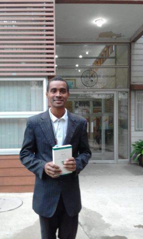 Jefferson de terno com um livro na mão.