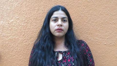Alba Calderón- mulher parda de cabelo longo, vestindo um vestido florido- em pé, apoiada em uma parede laranja.