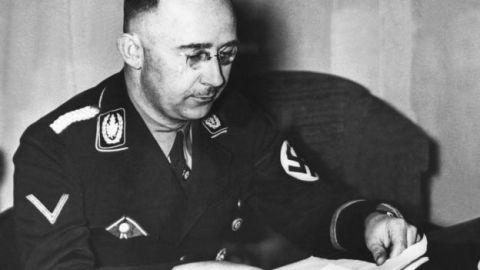 Imagem em preto e branco de Heinrich Himmler- homem branco, vestindo uniforme nazista e usando óculos- sentado olhando para um papel.