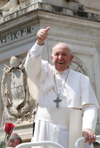 Papa Francisco- homem idoso branco, vestindo túnica branca e uma crus de prata- em pé sorrindo e acenando