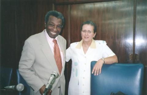 Milton Santos, homem negro d terno cinza, pousando para foto com Maria Adélia Souza, mulher branca de vestido branco