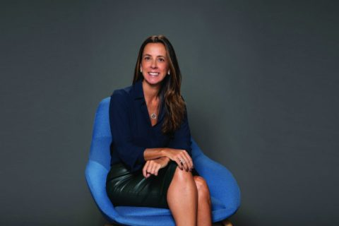 Ana Paula Bógus- mulher branca de cabelo longo, vestindo camisa social azul escuro e saia de couro- sentada em uma poltrona azul