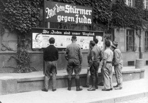 Foto em preto e branco de homens olhando um quadro de anúncios