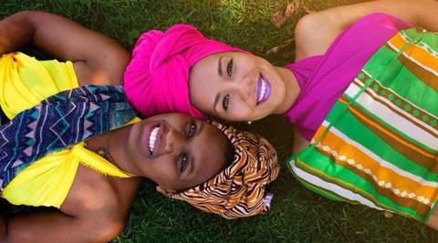 Denise de Oliveira e Raísa Amaral- mulheres negras, vestindo roupas coloridas característica africana, uma usando turbante com diversas cores e a outra usando um tubante rosa- deitadas na grama, uma paralela a outra