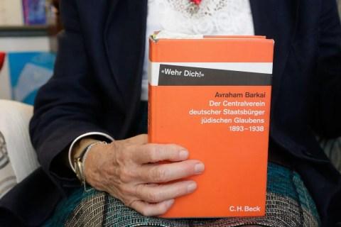 "Uma mão branca segurando o livro ""Der Centralverein deutscher Staatsburguer Júdschen Glaubens"""