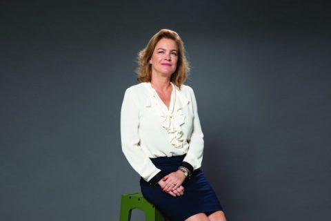 Sandrine Ferdane- mulher branca de cabelo loiro na altura dos ombros, vestindo camiseta branca e sia azul marinho- sentada em um banquinho verde