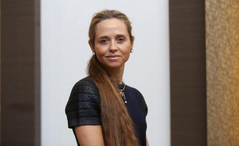 Patricia Villela Marino- mulher branca de cabelo longo loiro, vestindo um vestido preto- em pé