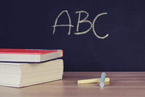 Uma mesa com giz e dois livros, ao fundo uma lousa com as letras ABC