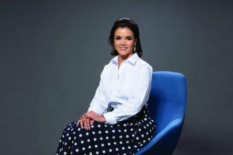 Ana Paula Assis- mulher branca de cabelo curto, vestindo uma camiseta branca e saia longa preta de bolinhas- sentada em uma poltrona azul