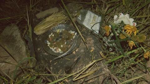 Imagem com oferendas da Casa do Caboclo em uma pedra.