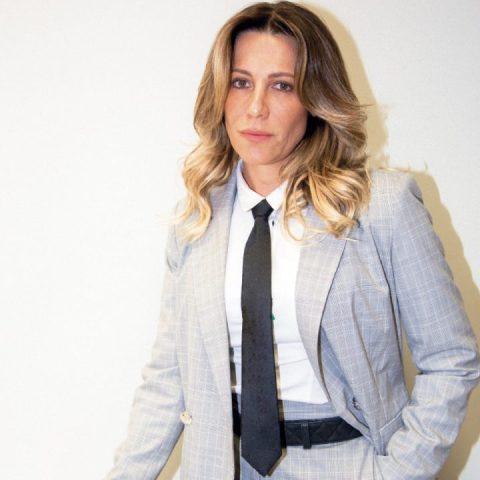 Gabriela Manssur- mulher branca de cabelo loiro na altura dos ombros, vestindo um terno- em pé com a mão no bolso