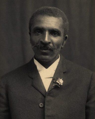 Fotografia de GEORGE WASHINGTON CARVER, homem negro, com pouco cabelo, bigode grande e vestindo um terno.