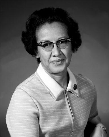 Fotografia em preto e branco de KATHERINE JOHNSON, sentada, vestindo camiseta listrada polo e óculos de grau