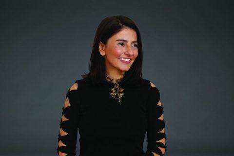 Alice Ferraz- mulher branca de cabelo na altura do ombro, vestindo um vestido preto- olhando para o lado e sorrindo