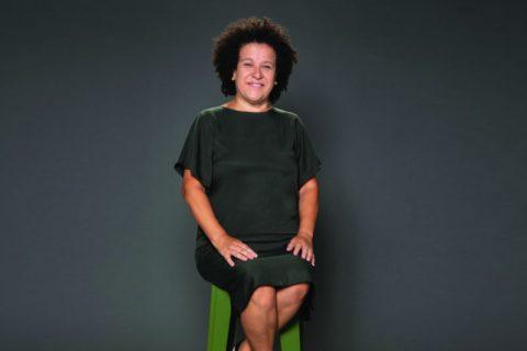 Ana Fontes- mulher branca de cabelo crespo, vestindo um vestido verde musgo- setada em um banquinho e sorrindo