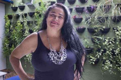 Maire Laide- mulher branca de cabelo longo na altura dos seios, vestindo camiseta regata preta e um colar grande- em pé fazendo pose com as mãos na cintura e sorrindo.