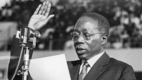 Fotografia em preto e branco de Léopond Sédar Senghor, homem negro, vestindo terno e usando óculos de grau, em pé discursando com a mão direita levantada.