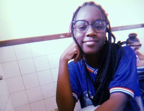 Quézia Ferreira, jovem negra, sentada com a mão no rosto utilizando óculos e uniforme escolar, em um ambiente q aparenta ser uma sala de aula.