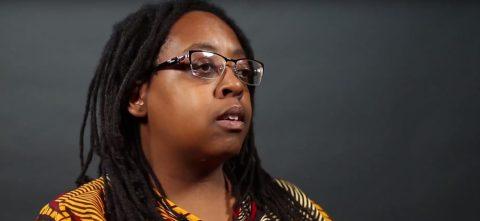 Cidinha da Silva- mulher negra de dreads, vestindo camiseta colorida e óculos de grau- sentada