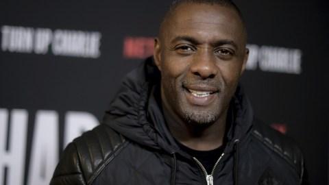 Idris Elba- homem negro alto, vestindo jaqueta preta- em pé sorrindo