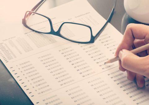 Uma mão com um lápis passando as respostas para o gabarito, e um óculos em cima da folha