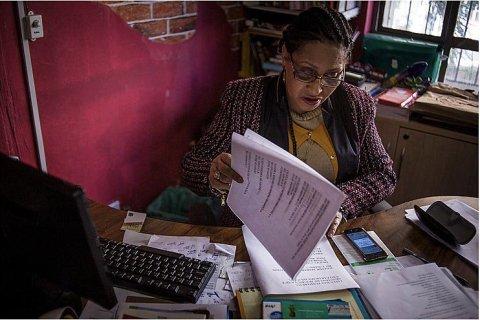 Carmen Silva-mulher negra idosa, vestindo casaco- sentada olhando documentos