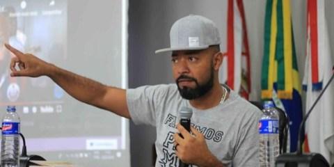 Douglas Belchior- homem negro, vestindo camiseta e boné cinza- discursando com um microfone na mão esquerda
