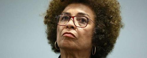 Angela Davis- mulher negra, de black power, usando óculos de grau- olhando para frente