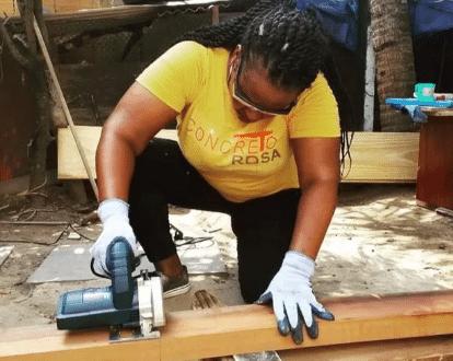 """Foto de uma mulher negra aguachada cortando um pedaço de madeira com makita, vestindo calça preta e camiseta amarela escrita """"Concreto Rosa"""""""