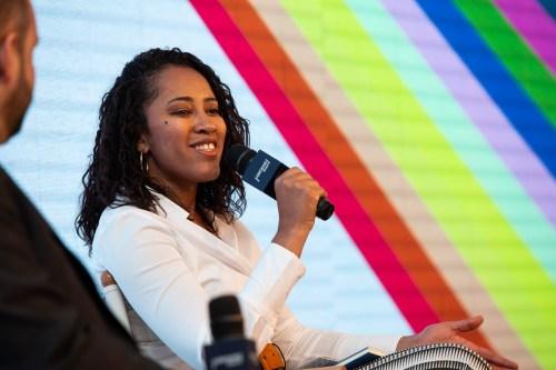 LILIANE ROCHA - mulher negra, de cabelo na altura dos ombros, vestindo camiseta branca- sentada com um microfone na mão