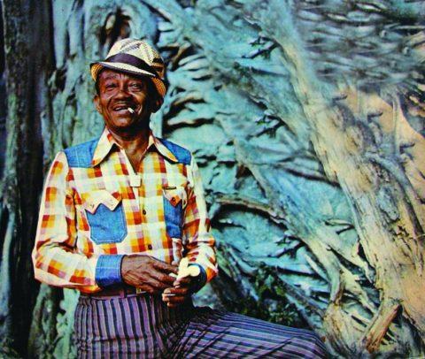 Foto de Jackson do Pandeiro- homem idoso negro, vestindo calça azul listrada, camiseta quadriculada colorida e chapéu- em pé com um cigarro na boca
