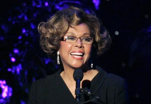 Diahann Carroll- mulher negra idosa, de cabelo cor de mel, usando roupa preta e óculos de grau- sorrindo em frente a um microfone.