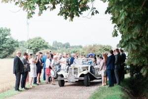 Bride and groom leaving in a car to reception