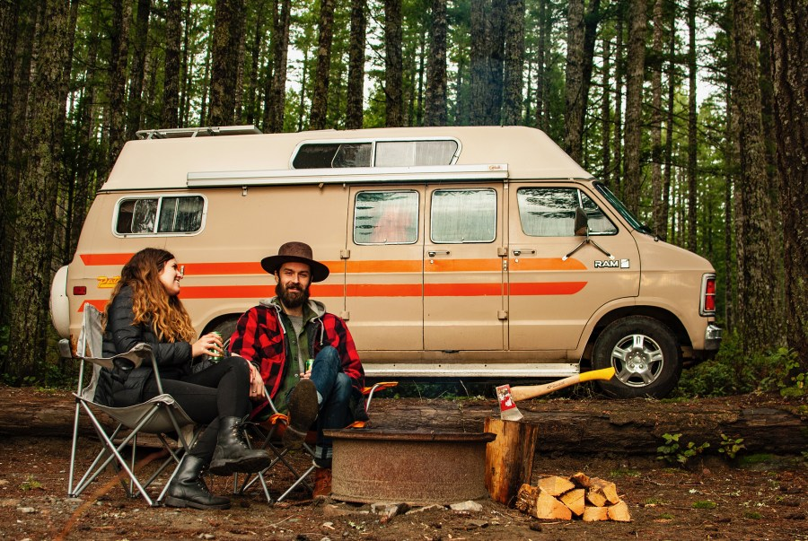 Van life couple sitting beside camper van and campfire - Guide to Van Life