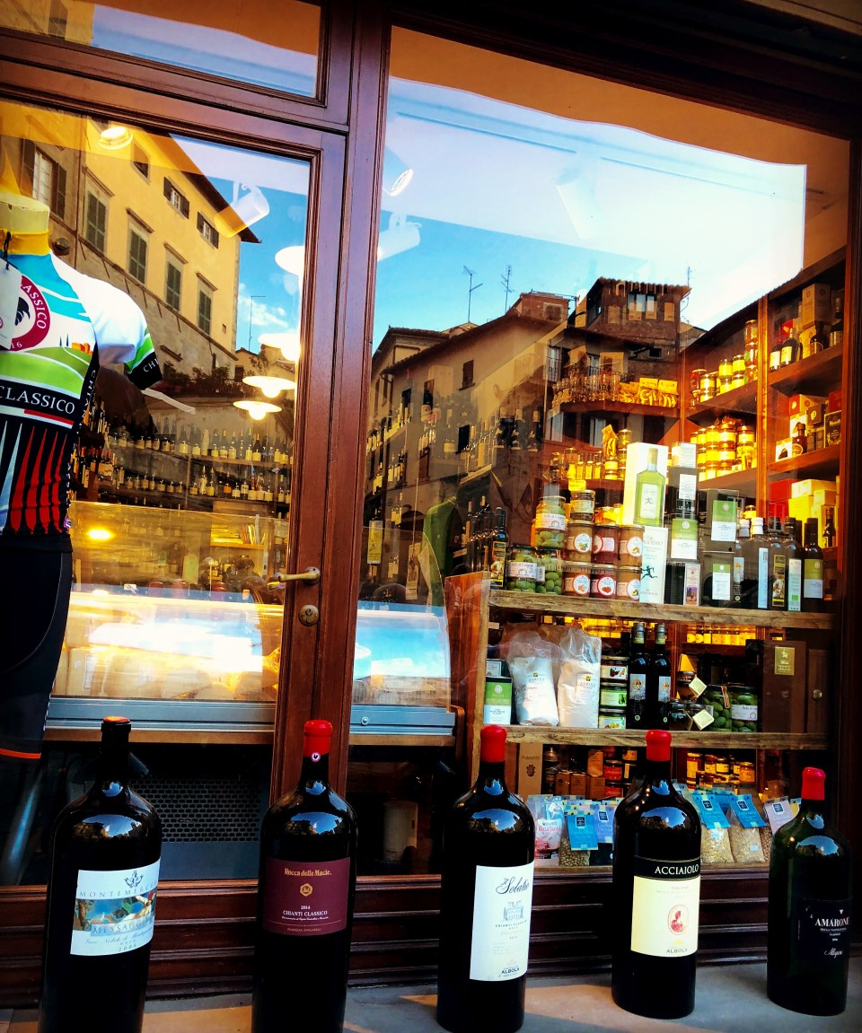 The plaza reflected in a wine shop window.