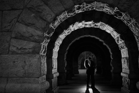 A black and white image of an engaged couple facing each other and standing under an arched stone tunnel in Lincoln Park.