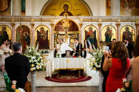 A image of a bride and groom holding candles circling the altar with the priest during a wedding ceremony inside the beautifully ornate Annunciation Greek Orthodox Church with colorful paintings and ornate stone pillars with gold trim throughout the sanctuary.
