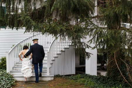 A image from behind of a bride in her white gown ascending the white rounded steps of the Chagrin Valley Athletic Club while her groom has his arm around her wearing his military dress blues assisting her with green pine trees in the foreground and ivy growing in the background.