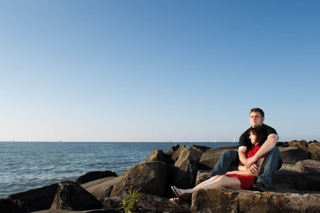 An image of an engaged couple where the woman is wearing a red dress and sitting snuggled in-between the man's jean-clad legs and black t-shirted arms on large rocks overlooking Lake Erie on the shores of Edgewater Park on a sunny and blue sky evening.