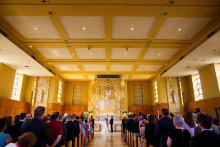 A picture of a bride and groom standing at the altar of the brightly lit yellow sanctuary of Gesu Church with the square ceiling pattern while the guests stand at the pews overlooking the couple.