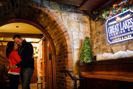 An engaged couple embrace in the left of the picture while standing under the arched brick entryway to the Great Lakes Brewing Company where the blue lit-up sign is mounted in the right of the picture to a stone wall.