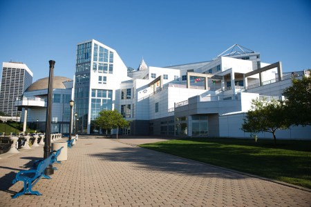An outdoor shot taken of the back of the Great Lakes Science Center's white and glass multi-level building with a brick sidewalk and blue wrought-iron benches overlooking the water of Lake Erie on a sunny and blue sky day.