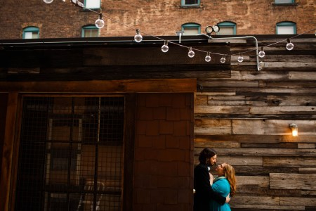 An engagent couple embrace where the woman is wearing a teal dress and the man is in a black suit coat leaning against the outside corner of a wooden-planked wall with and a cedar shingled entryway with cafe lights draped from above at the Greenhouse Tavern.
