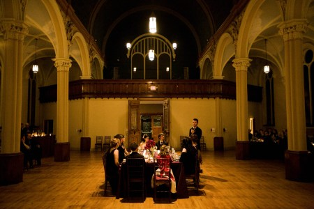 A wedding party is seated at a square head table set in the middle of the room at the Josaphat Art Hall with light colored ornate arched pillars and dark trim set around the room and a lighter colored wooden floor.