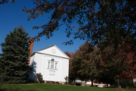 A picture of the small white Leroy United Methodist Church in the lower left of the photo sitting next to a tall pine tree on the left and taller maple trees on the right taken on a bright sunny fall day with under a brilliantly blue sky with leave from another tree hanging down in the upper right of the photo.