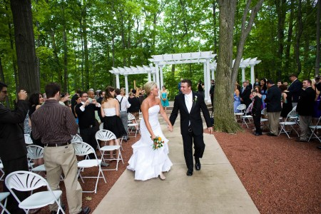 A picture of a bride and groom walking back down the outdoor aisle at Manakiki Golf Course in Willoughby, Ohio with guests standing from their seats on either wide while the couple is holding hands and laughing with a white arbor in the background under a canopy of tall green trees.
